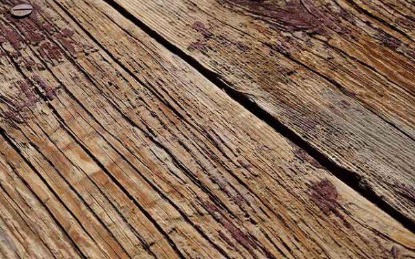 Brett aus altem Holz, in dem in der linken oberen Ecke ein Nagel sichtbar ist