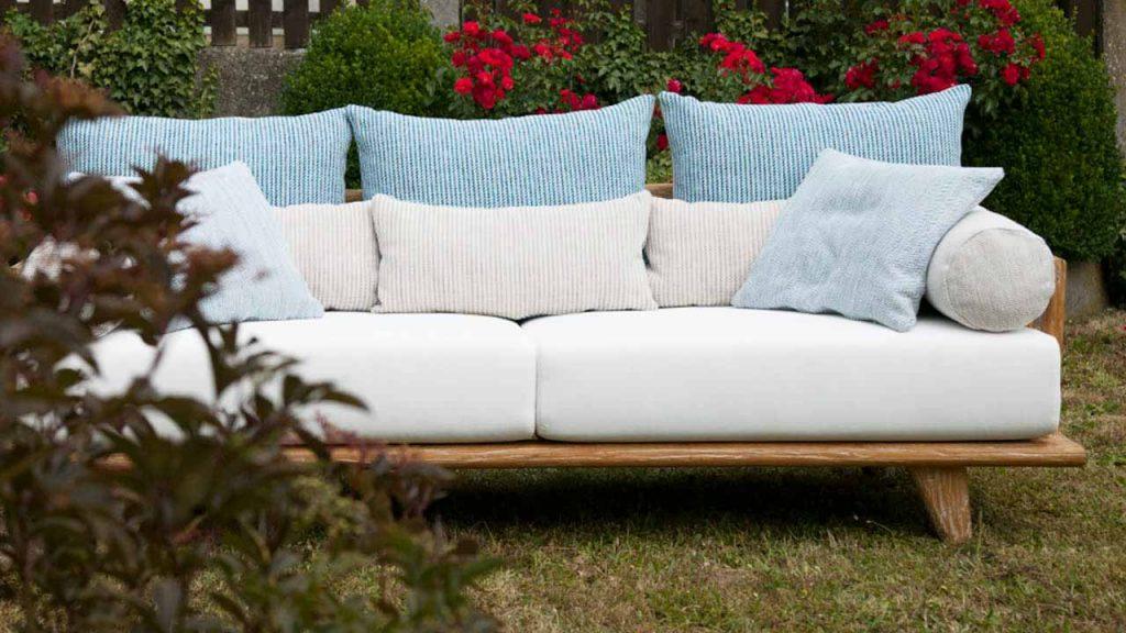 Sofa COMO im Garten von vorne fotografiert; linke Armlehne durch Strauch verdeckt